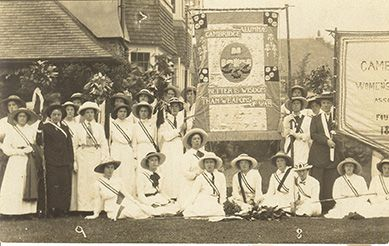 A photograph from the Newnham archives of a group of women students, carrying the Cambridge Alumnae suffrage banner.