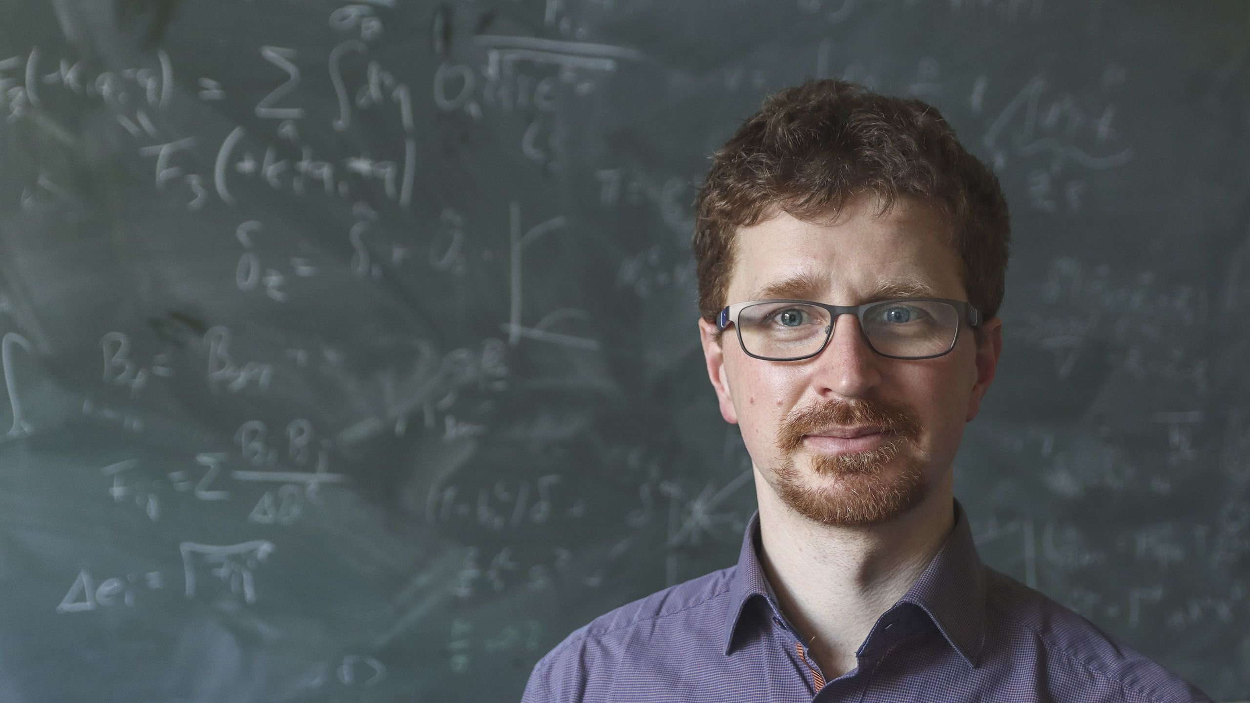Dr Tobias Baldauf standing in front of a blackboard with equations written on it in chalk
