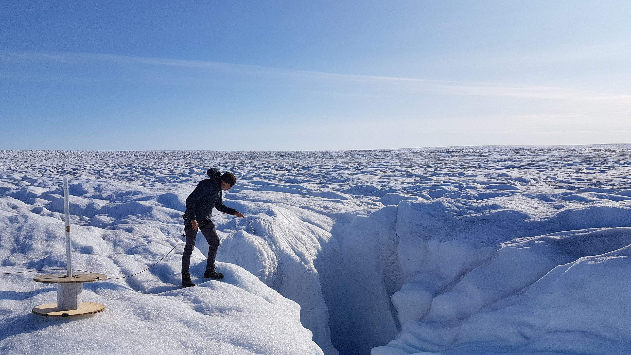 Scientist installs fibre-optic cable on the Greenland Ice Sheet