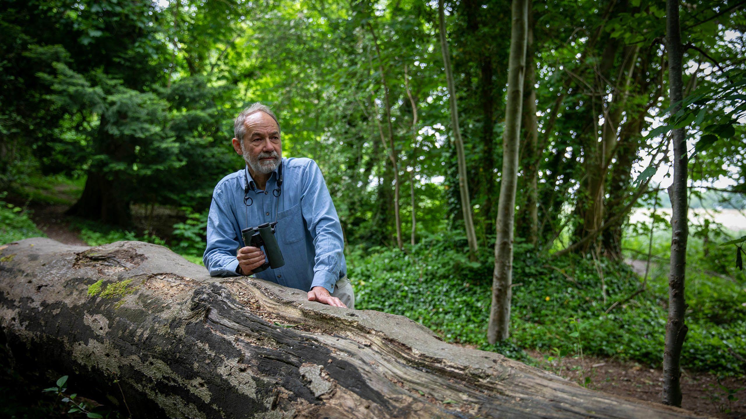 Bill leaning on fallen tree trunk