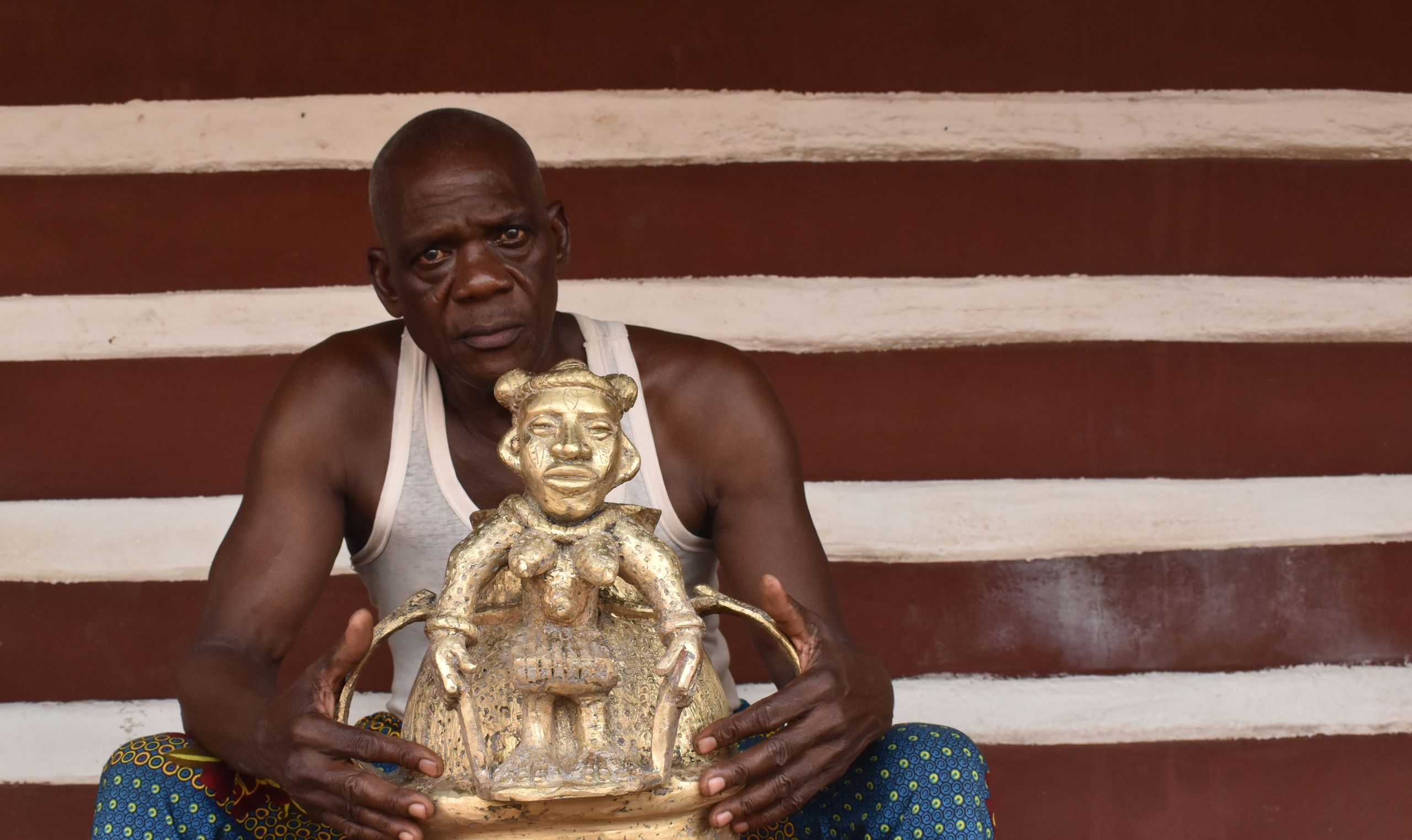 Mark Ihama, brass-caster of Igun Street, Benin City with the brass reproduction Olokun pot made for the [Re:]Entanglements exhibition. Image: Paul Basu