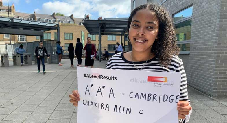 A student smiling holding their A Level results up.