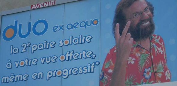 It's a rude gesture in the UK; in this French poster it advertises two pairs of sunglasses for the price of one