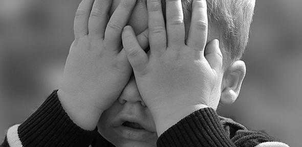 Child with hands over face - children may be at risk by too much focus on COVID-19