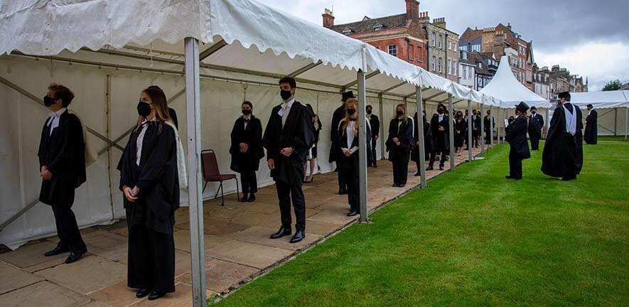 Graduands in academic dress for graduation standing in a socially distanced queue wearing masks