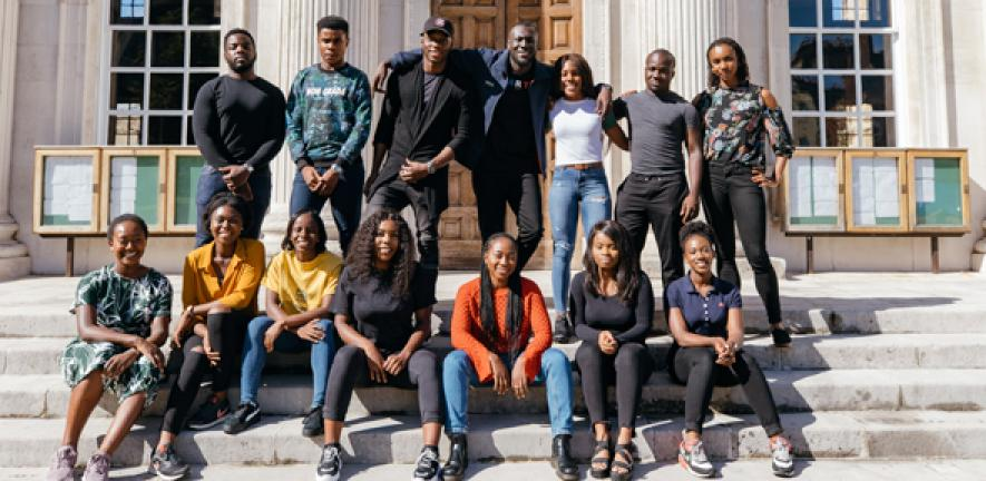 Stormzy with Cambridge students on the steps of Senate House at the University