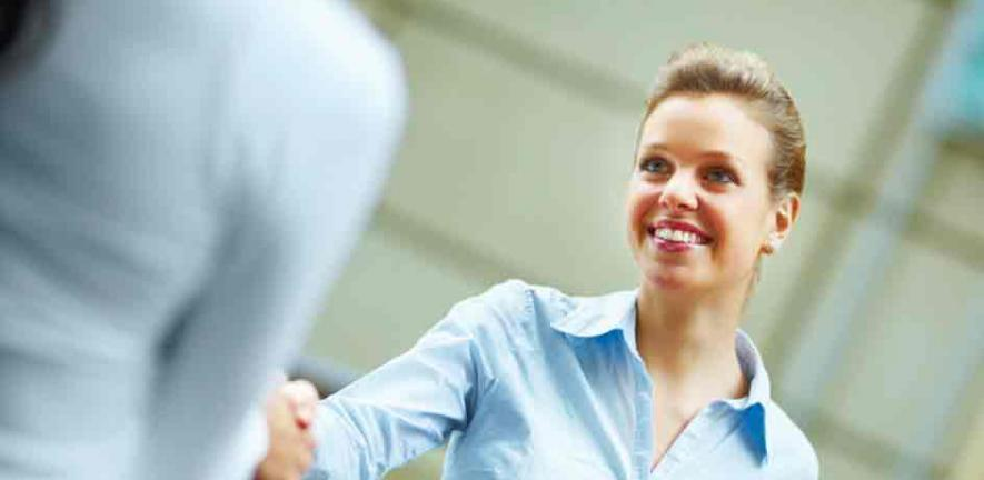Happy young business woman shaking hands with another female