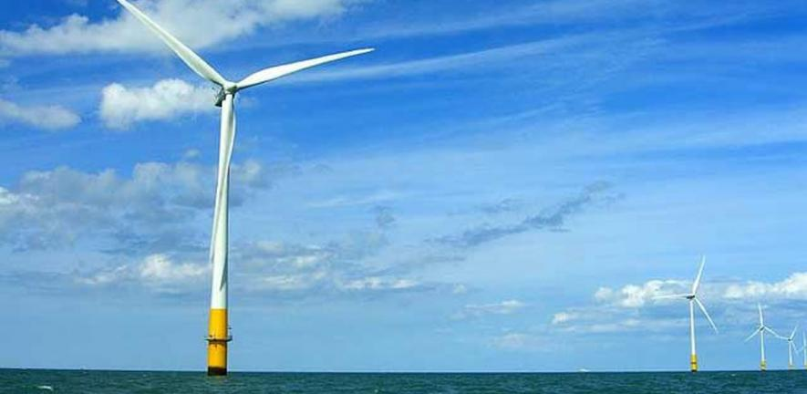 Wind turbines in the Thames estuary with heavy supporting structures under water.