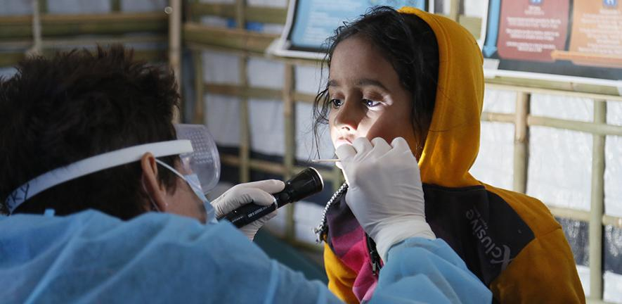 UK Emergency Medical Team paediatric nurse checks a girl for symptoms of Diphtheria in the Kutapalong refugee camp, Bangladesh