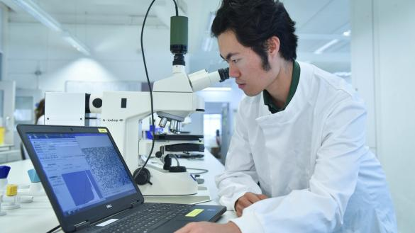 A student with scientific equipment and a laptop