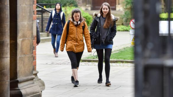 Two students walking across cobbles