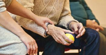 Woman touching the arm of an elderly man holding a juggling ball