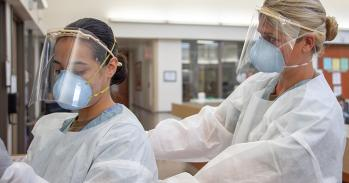 Medical personnel putting on PPE