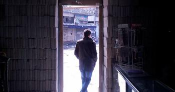 Man framed in pharmacy entrance, in Syria
