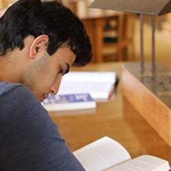 Student at a desk reading a book