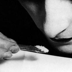 A close up of a young woman snorting cocaine during the 1920s