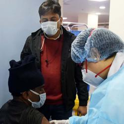 Health care workers administering covid-19 vaccination in New Delhi