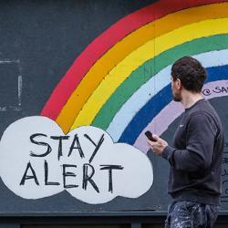 Man walking past Stay Alert/Save Lives artwork