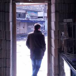 Man framed in pharmacy entrance, in Syria